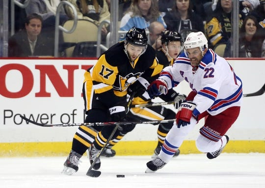 Feb 10, 2016; Pittsburgh, PA, USA; Pittsburgh Penguins right wing Bryan Rust (17) carries the puck as New York Rangers defenseman Dan Boyle (22) defends during the first period at the CONSOL Energy Center. Mandatory Credit: Charles LeClaire-USA TODAY Sports