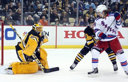 Feb 10, 2016; Pittsburgh, PA, USA; Pittsburgh Penguins goalie Marc-Andre Fleury (29) makes a blocking pad save in front of New York Rangers center Derick Brassard (16) and Penguins defenseman Olli Maatta (3) during the first period at the CONSOL Energy Center. Mandatory Credit: Charles LeClaire-USA TODAY Sports