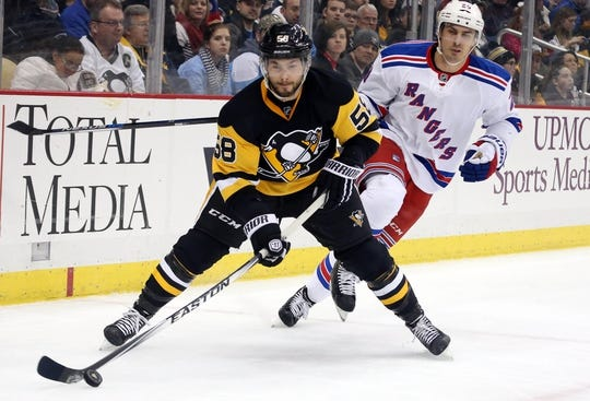 Feb 10, 2016; Pittsburgh, PA, USA; Pittsburgh Penguins defenseman Kris Letang (58) handles the puck ahead of New York Rangers left wing Chris Kreider (20) during the first period at the CONSOL Energy Center. Mandatory Credit: Charles LeClaire-USA TODAY Sports