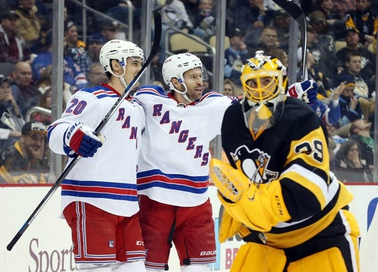 Feb 10, 2016; Pittsburgh, PA, USA; New York Rangers left wing Chris Kreider (20) and center Dominic Moore (C) celebrate after Moore scored a goal against Pittsburgh Penguins goalie Marc-Andre Fleury (29) during the third period at the CONSOL Energy Center. The Rangers shutout the Penguins 3-0. Mandatory Credit: Charles LeClaire-USA TODAY Sports