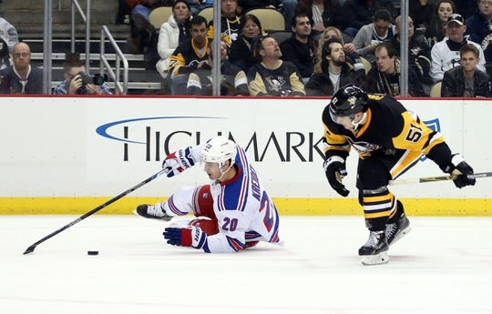 Feb 10, 2016; Pittsburgh, PA, USA; New York Rangers left wing Chris Kreider (20) reaches for the puck after being knocked down by Pittsburgh Penguins defenseman Derrick Pouliot (51) during the third period at the CONSOL Energy Center. The Rangers shutout the Penguins 3-0. Mandatory Credit: Charles LeClaire-USA TODAY Sports