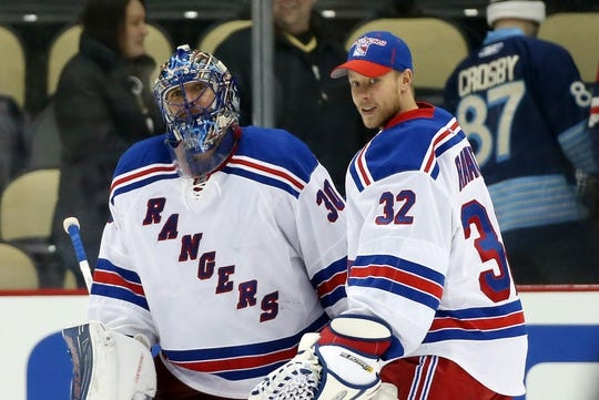 Feb 10, 2016; Pittsburgh, PA, USA; New York Rangers goalies Henrik Lundqvist (30) and Antti Raanta (32) celebrate after defeating the Pittsburgh Penguins at the CONSOL Energy Center. The Rangers shutout the Penguins 3-0. Mandatory Credit: Charles LeClaire-USA TODAY Sports