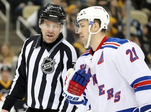 Feb 10, 2016; Pittsburgh, PA, USA; NHL linesman Michel Cormier (L) talks with New York Rangers center Derek Stepan (21) during a stoppage in play against the Pittsburgh Penguins in the second period at the CONSOL Energy Center. The Rangers won 3-0. Mandatory Credit: Charles LeClaire-USA TODAY Sports