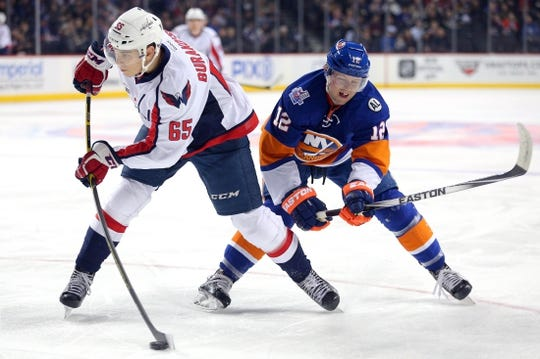 Feb 18, 2016; Brooklyn, NY, USA; Washington Capitals left wing Andre Burakovsky (65) shoots in front of New York Islanders left wing Josh Bailey (12) during the first period at Barclays Center. Mandatory Credit: Brad Penner-USA TODAY Sports