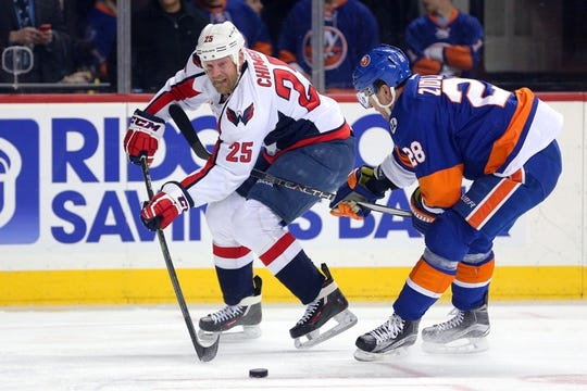 Feb 18, 2016; Brooklyn, NY, USA; Washington Capitals left wing Jason Chimera (25) controls the puck against New York Islanders defenseman Marek Zidlicky (28) during the first period at Barclays Center. Mandatory Credit: Brad Penner-USA TODAY Sports