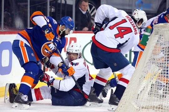 Feb 18, 2016; Brooklyn, NY, USA; New York Islanders defenseman Brian Strait (37) fights for a puck against Washington Capitals left wing Alex Ovechkin (8) and right wing Justin Williams (14) during the first period at Barclays Center. Mandatory Credit: Brad Penner-USA TODAY Sports
