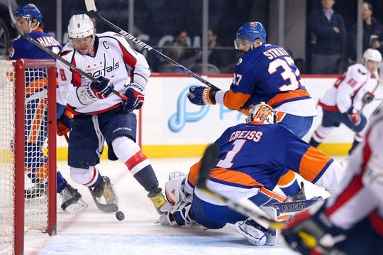 Feb 18, 2016; Brooklyn, NY, USA; New York Islanders goalie Thomas Greiss (1) makes a save against Washington Capitals left wing Alex Ovechkin (8) in front of New York Islanders defenseman Brian Strait (37) during the first period at Barclays Center. Mandatory Credit: Brad Penner-USA TODAY Sports