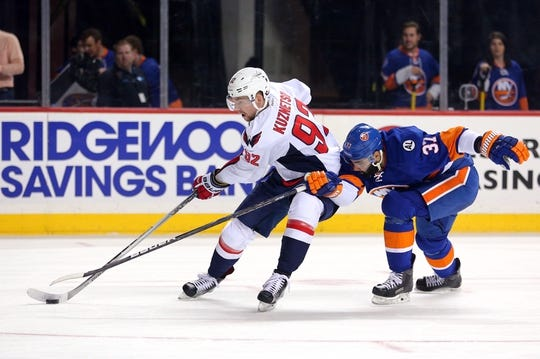 Feb 18, 2016; Brooklyn, NY, USA; Washington Capitals center Evgeny Kuznetsov (92) controls the puck against New York Islanders defenseman Brian Strait (37) during the first period at Barclays Center. Mandatory Credit: Brad Penner-USA TODAY Sports