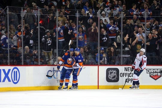 Feb 18, 2016; Brooklyn, NY, USA; New York Islanders center John Tavares (91) celebrates his goal in front of Washington Capitals defenseman Nate Schmidt (88) with New York Islanders center Mikhail Grabovski (84) during the first period at Barclays Center. Mandatory Credit: Brad Penner-USA TODAY Sports