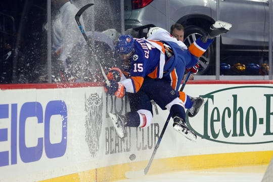 Feb 18, 2016; Brooklyn, NY, USA; New York Islanders right wing Cal Clutterbuck (15) hits Washington Capitals defenseman Dmitry Orlov (9) during the second period at Barclays Center. Mandatory Credit: Brad Penner-USA TODAY Sports