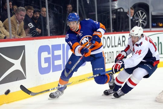 Feb 18, 2016; Brooklyn, NY, USA; New York Islanders defenseman Travis Hamonic (3) passes the puck against Washington Capitals right wing Justin Williams (14) during the third period at Barclays Center. The Capitals defeated the Islanders 3-2 in overtime. Mandatory Credit: Brad Penner-USA TODAY Sports