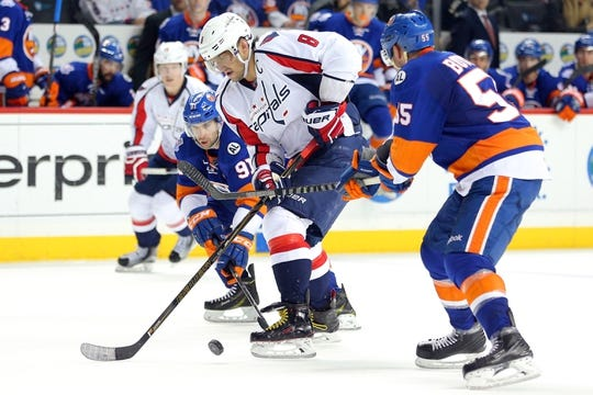 Feb 18, 2016; Brooklyn, NY, USA; Washington Capitals left wing Alex Ovechkin (8) skates the puck between New York Islanders center John Tavares (91) and defenseman Johnny Boychuk (55) during the third period at Barclays Center. The Capitals defeated the Islanders 3-2 in overtime. Mandatory Credit: Brad Penner-USA TODAY Sports