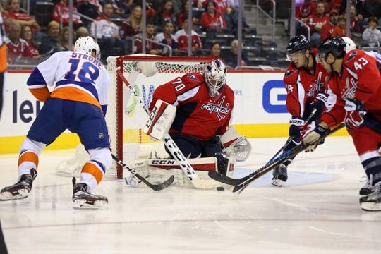 Oct 15, 2016; Washington, DC, USA; Washington Capitals goalie Braden Holtby (70) makes a save on New York Islanders right wing Ryan Strome (18) in the second period at Verizon Center. Mandatory Credit: Geoff Burke-USA TODAY Sports