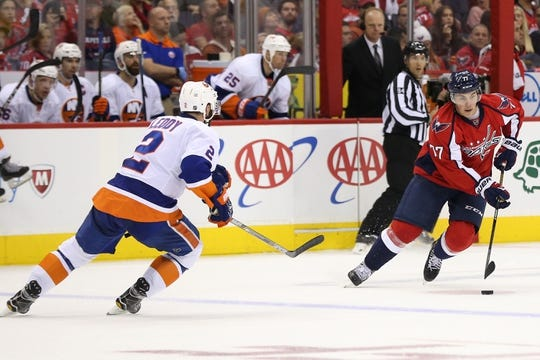 Oct 15, 2016; Washington, DC, USA; Washington Capitals right wing T.J. Oshie (77) skates with the puck as New York Islanders defenseman Nick Leddy (2) defends in the third period at Verizon Center. The Capitals won 2-1. Mandatory Credit: Geoff Burke-USA TODAY Sports