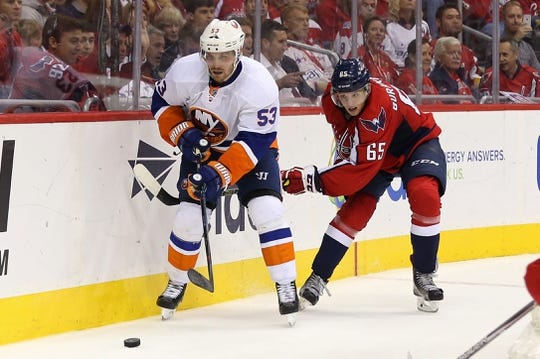 Oct 15, 2016; Washington, DC, USA; New York Islanders center Casey Cizikas (53) and Washington Capitals left wing Andre Burakovsky (65) battle for the puck in the third period at Verizon Center. The Capitals won 2-1. Mandatory Credit: Geoff Burke-USA TODAY Sports