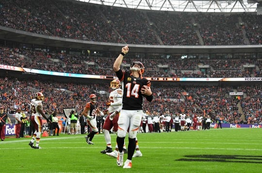 Oct 30, 2016; London, United Kingdom; Cincinnati Bengals quarterback Andy Dalton (14) celebrates after scoring on a one-yard touchdown run in the third quarter during game 17 of the NFL International Series at Wembley Stadium. The Redskins and Bengals tied 27-27. Mandatory Credit: Kirby Lee-USA TODAY Sports