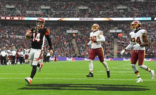Oct 30, 2016; London, United Kingdom; Cincinnati Bengals quarterback Andy Dalton (14) is pursued by Washington Redskins defensive end Matt Ioannidis (98) and cornerback Josh Norman (24) on a one-yard touchdown run in the third quarter during game 17 of the NFL International Series at Wembley Stadium. The Redskins and Bengals tied 27-27. Mandatory Credit: Kirby Lee-USA TODAY Sports
