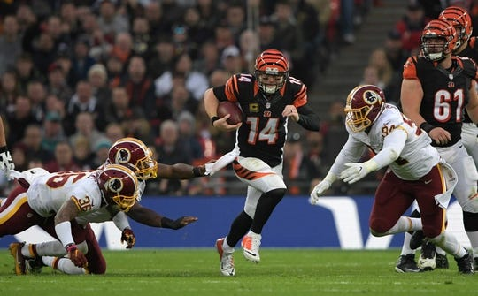 Oct 30, 2016; London, United Kingdom; Cincinnati Bengals quarterback Andy Dalton (14) is defended by Washington Redskins safety Su'a Cravens (36) and linebacker Preston Smith (94) on a 14-yard rush during game 17 of the NFL International Series at Wembley Stadium. The Redskins and Bengals tied 27-27. Mandatory Credit: Kirby Lee-USA TODAY Sports