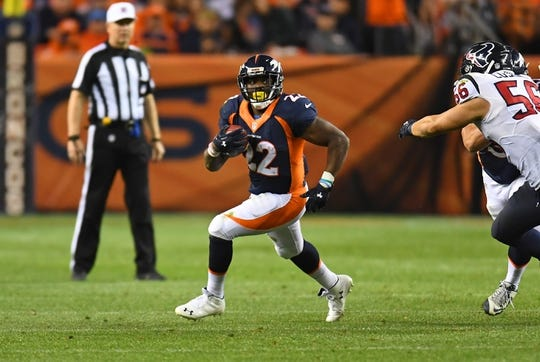 Oct 24, 2016; Denver, CO, USA; Denver Broncos running back C.J. Anderson (22) carries the ball away from Houston Texans inside linebacker Brian Cushing (56) in the second half at Sports Authority Field at Mile High. The Broncos defeated the Texans 27-9. Mandatory Credit: Ron Chenoy-USA TODAY Sports