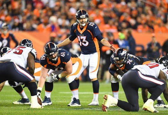 Oct 24, 2016; Denver, CO, USA; Denver Broncos quarterback Trevor Siemian (13) calls out an audible behind center Matt Paradis (61) and offensive guard Max Garcia (76) in the second half against the Houston Texans at Sports Authority Field at Mile High. The Broncos defeated the Texans 27-9. Mandatory Credit: Ron Chenoy-USA TODAY Sports