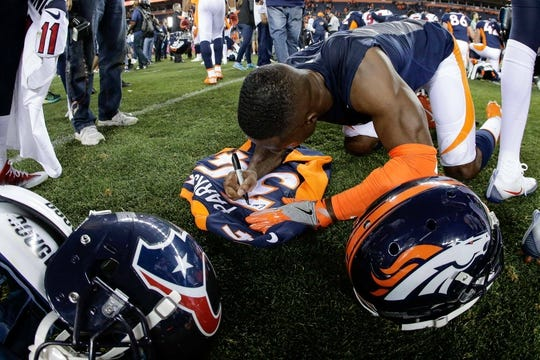 Oct 24, 2016; Denver, CO, USA; Denver Broncos strong safety T.J. Ward (43) signs his jersey after the game against the Houston Texans at Sports Authority Field at Mile High. Mandatory Credit: Isaiah J. Downing-USA TODAY Sports