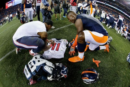 Oct 24, 2016; Denver, CO, USA; Houston Texans wide receiver Jaelen Strong (11) and Denver Broncos strong safety T.J. Ward (43) sign their jerseys before swapping them after the game at Sports Authority Field at Mile High. Mandatory Credit: Isaiah J. Downing-USA TODAY Sports