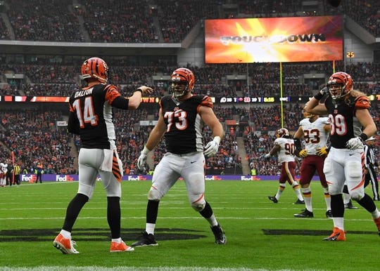 Oct 30, 2016; London, United Kingdom; Cincinnati Bengals quarterback Andy Dalton (14) celebrates with guard Eric Winston (73) after scoring on a 1-yard touchdown run in the third quarter against the Washington Redskins during game 17 of the NFL International Series at Wembley Stadium. The Redskins and Bengals tied 27-27 tie. Mandatory Credit: Kirby Lee-USA TODAY Sports