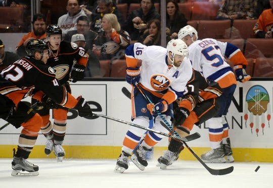 November 22, 2016; Anaheim, CA, USA;  New York Islanders left wing Andrew Ladd (16) moves the puck against the defense of Anaheim Ducks defenseman Josh Manson (42) during the first period at Honda Center. Mandatory Credit: Gary A. Vasquez-USA TODAY Sports