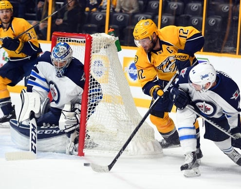 Nov 25, 2016; Nashville, TN, USA; Nashville Predators center Mike Fisher (12) carries the puck around the net to attempt a shot on Winnipeg Jets goalie Connor Hellebuyck (37) during the first period at Bridgestone Arena. Mandatory Credit: Christopher Hanewinckel-USA TODAY Sports