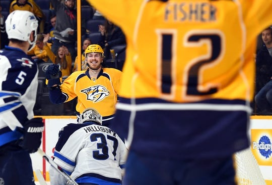 Nov 25, 2016; Nashville, TN, USA; Nashville Predators left wing Colin Wilson (33) celebrates after scoring a goal with an assist from center Mike Fisher (12) during the third period against the Winnipeg Jets at Bridgestone Arena. The Predators won 5-1. Mandatory Credit: Christopher Hanewinckel-USA TODAY Sports