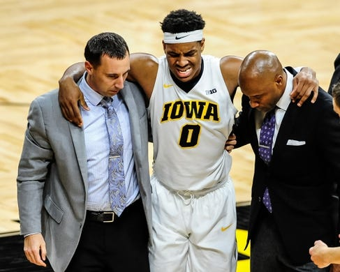 Dec 5, 2016; Iowa City, IA, USA; Injured Iowa Hawkeyes forward Ahmad Wagner (0) is assisted by the Iowa trainer (left) and assistant coach Andrew Francis (right) during the second half against the Stetson Hatters at Carver-Hawkeye Arena. Mandatory Credit: Jeffrey Becker-USA TODAY Sports