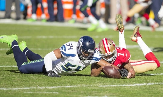 Jan 1, 2017; Santa Clara, CA, USA; San Francisco 49ers quarterback Colin Kaepernick (7) dives after the fumble against Seattle Seahawks middle linebacker Bobby Wagner (54) during the first quarter at Levis Stadium. Mandatory Credit: Neville E. Guard-USA TODAY Sports