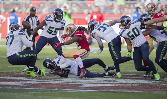 Jan 1, 2017; Santa Clara, CA, USA; San Francisco 49ers running back DuJuan Harris (32) fumbles the football against Seattle Seahawks strong safety Kam Chancellor (31) during the second quarter at Levis Stadium. Mandatory Credit: Neville E. Guard-USA TODAY Sports