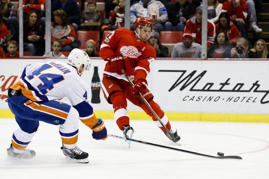 Feb 3, 2017; Detroit, MI, USA; Detroit Red Wings center Dylan Larkin (71) takes a shot defended by New York Islanders defenseman Calvin de Haan (44) in the first period at Joe Louis Arena. Mandatory Credit: Rick Osentoski-USA TODAY Sports