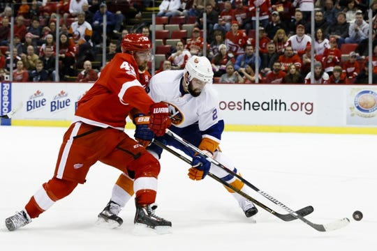 Feb 3, 2017; Detroit, MI, USA; Detroit Red Wings center Darren Helm (43) and New York Islanders defenseman Nick Leddy (2) battle for the puck in the second period at Joe Louis Arena. Mandatory Credit: Rick Osentoski-USA TODAY Sports