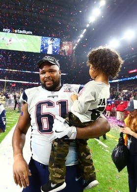 Feb 5, 2017; Houston, TX, USA; New England Patriots offensive lineman Marcus Cannon (61) holds son Marcus Cannon Jr as he celebrates after defeating the Atlanta Falcons during Super Bowl LI at NRG Stadium. Mandatory Credit: Mark J. Rebilas-USA TODAY Sports