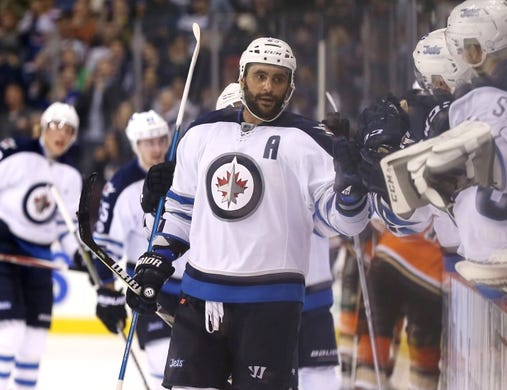 Mar 30, 2017; Winnipeg, Manitoba, CAN; Winnipeg Jets defenseman Dustin Byfuglien (33) celebrates his goal with teammates during the third period against the Anaheim Ducks at MTS Centre. The Jets won 4-3 in overtime. Mandatory Credit: Bruce Fedyck-USA TODAY Sports