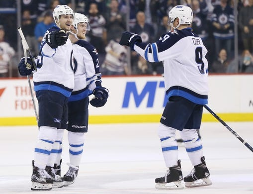 Mar 30, 2017; Winnipeg, Manitoba, CAN; Winnipeg Jets center Mark Scheifele (55) celebrates his goal with teammates  during the overtime period against the Anaheim Ducks  at MTS Centre. The Jets won 4-3 in overtime. Mandatory Credit: Bruce Fedyck-USA TODAY Sports