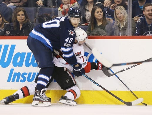Apr 1, 2017; Winnipeg, Manitoba, CAN;  Winnipeg Jets right wing Joel Armia (40) pins Ottawa Senators center Kyle Turris (7) against the boards during the third period at MTS Centre. Winnipeg won 4-2. Mandatory Credit: Bruce Fedyck-USA TODAY Sports