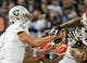 Oct 19, 2017; Oakland, CA, USA; Kansas City Chiefs reach for the wrist of Oakland Raiders quarterback Derek Carr (4) during the second quarter at Oakland Coliseum. Mandatory Credit: Kelley L Cox-USA TODAY Sports