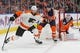 Dec 14, 2018; Edmonton, Alberta, CAN; Philadelphia Flyers forward Sean Couturier (14) and Edmonton Oilers forward Ryan Nugent-Hopkins (93) battle for a loose puck during the second period at Rogers Place. Mandatory Credit: Perry Nelson-USA TODAY Sports