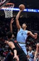 Apr 3, 2019; Portland, OR, USA;Memphis Grizzlies forward Bruno Caboclo (5) goes up for a shot over Portland Trail Blazers guard Evan Turner (1) during the first half of the game at the Moda Center. Mandatory Credit: Steve Dykes-USA TODAY Sports
