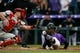 Apr 20, 2019; Denver, CO, USA; Philadelphia Phillies catcher J.T. Realmuto (10) is unable to field the ball as Colorado Rockies left fielder Raimel Tapia (15) slides into home plate on an inside the park home run in the second inning at Coors Field. Mandatory Credit: Isaiah J. Downing-USA TODAY Sports