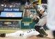 May 19, 2019; Detroit, MI, USA; Detroit Tigers shortstop Niko Goodrum (28) scores a run against Oakland Athletics catcher Josh Phegley (19) in the first inning at Comerica Park. Mandatory Credit: Rick Osentoski-USA TODAY Sports