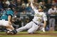 Jul 5, 2019; Seattle, WA, USA; Oakland Athletics first baseman Matt Olson (28) slides home to score a run as Seattle Mariners catcher Tom Murphy (2) attempts to corral a throwing error by a teammate during the seventh inning at T-Mobile Park. Mandatory Credit: Joe Nicholson-USA TODAY Sports