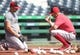 Aug 25, 2019; Pittsburgh, PA, USA;  Cincinnati Reds infielder Kyle Farmer (L) works with third base/catching coach J.R. House (R) before playing the Pittsburgh Pirates in a MLB Players' Weekend game at PNC Park. Mandatory Credit: Charles LeClaire-USA TODAY Sports