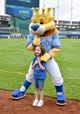 Sep 1, 2019; Kansas City, MO, USA; The Kansas City Royals mascot Sluggerrr poses for a photo with a young fan on the warning track before a game against the Baltimore Orioles at Kauffman Stadium. Mandatory Credit: Denny Medley-USA TODAY Sports